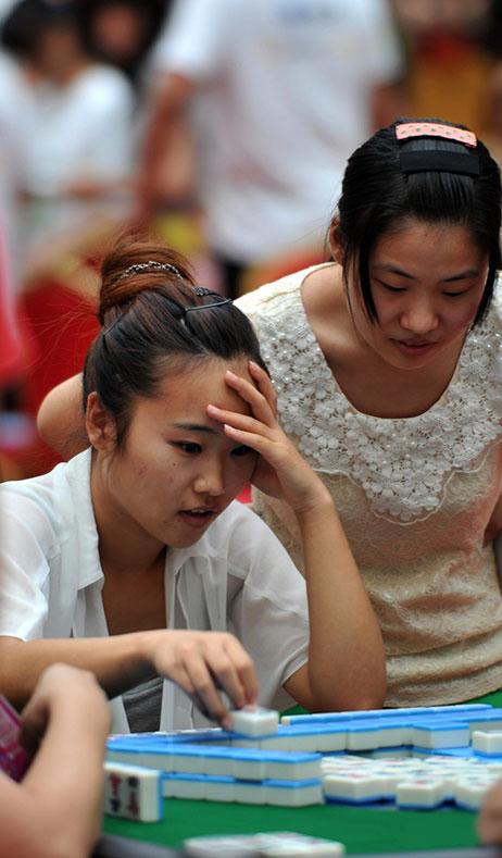 Tournoi de Mah-Jong à Wuhan. Rassemblement de 10 000 joueurs amateurs et professionnels confondus pour tenter le record du monde. Photo prise le 24 Aout 2013. Photo CNS : Zhang Chang. Femmes jouant au Mah ong et qui réfléchissent